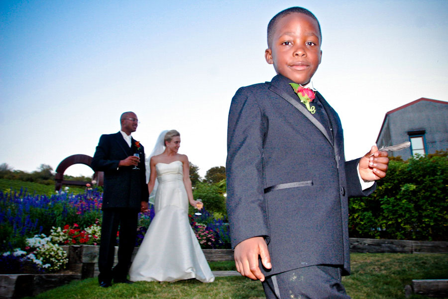ring bearer stands in front of bride and groom