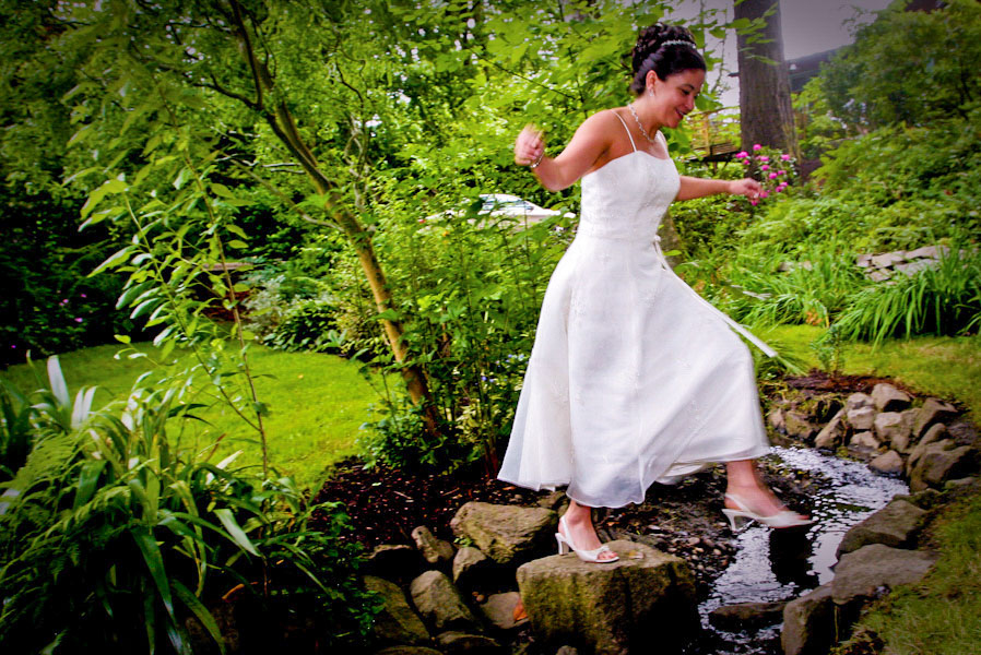 bride steps on rock-jumping-over-creek outdoor wedding