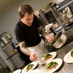 Chef Aaron Solley at James John Cafe setting course plates out in kitchen
