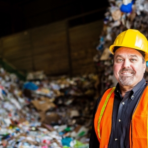 CEO of Farwest Fibers standing before mountain of recycling