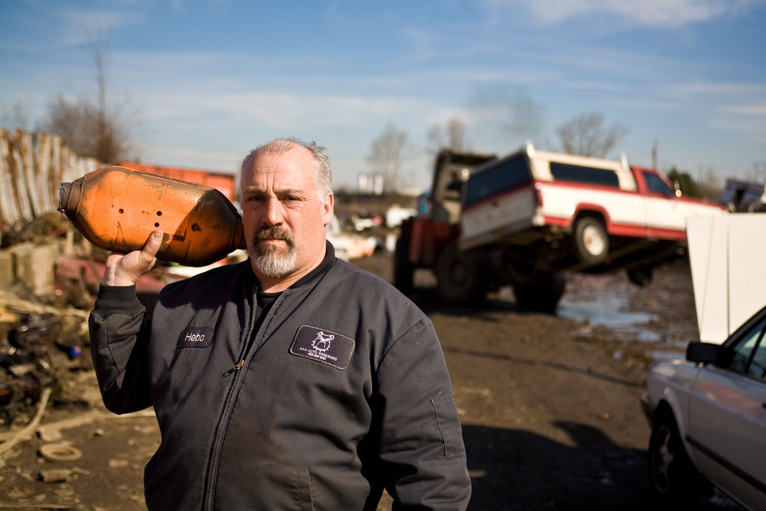 Heber Thurston, owner of AAA Auto Wrecking holds a catalytic converter in Portland junkyard