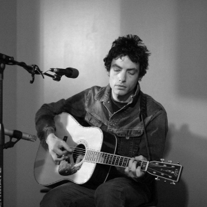 Jakob Dylan strumming guitar during a live performance for Kink 101.9 fm