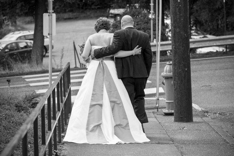 Bride and Groom seen from behind walking arm in arm down street