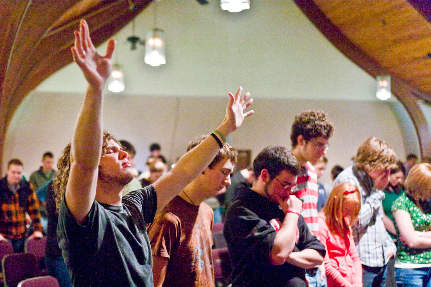 Man raises hand while others pray at the Red Sea Church in St. Johns Oregon
