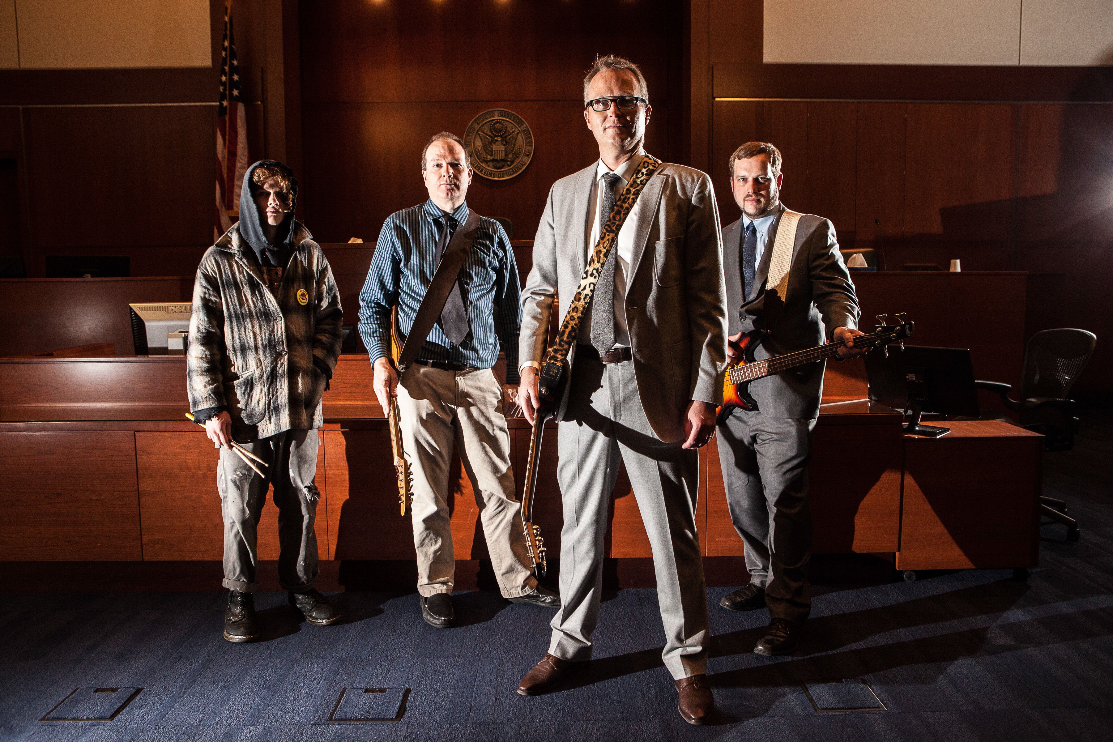 Band of Lawyers standing in courtroom with guitars in Oregon
