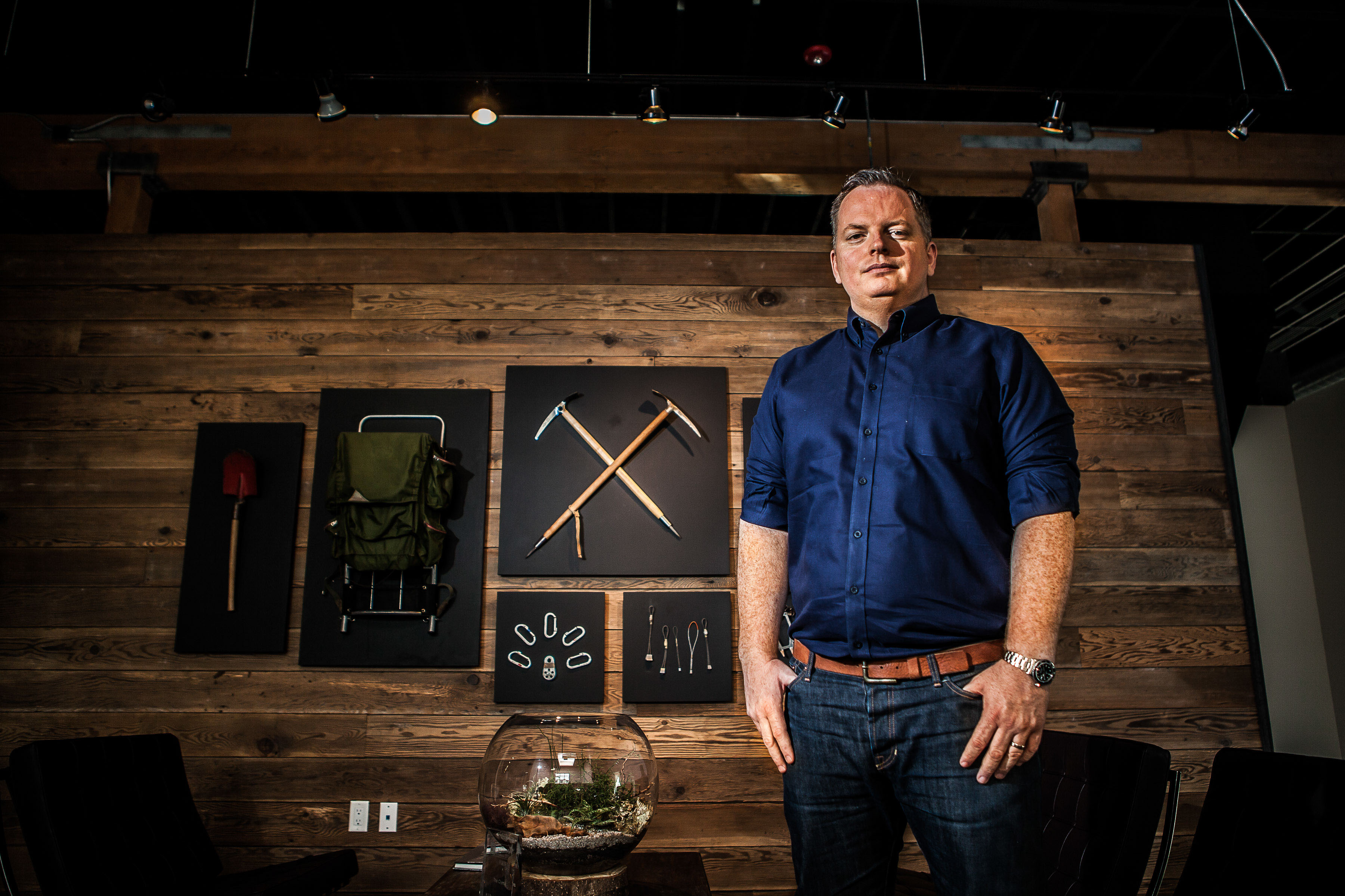 Ceo of Outdoor Equipment company stand in front of mounted equipment on wall