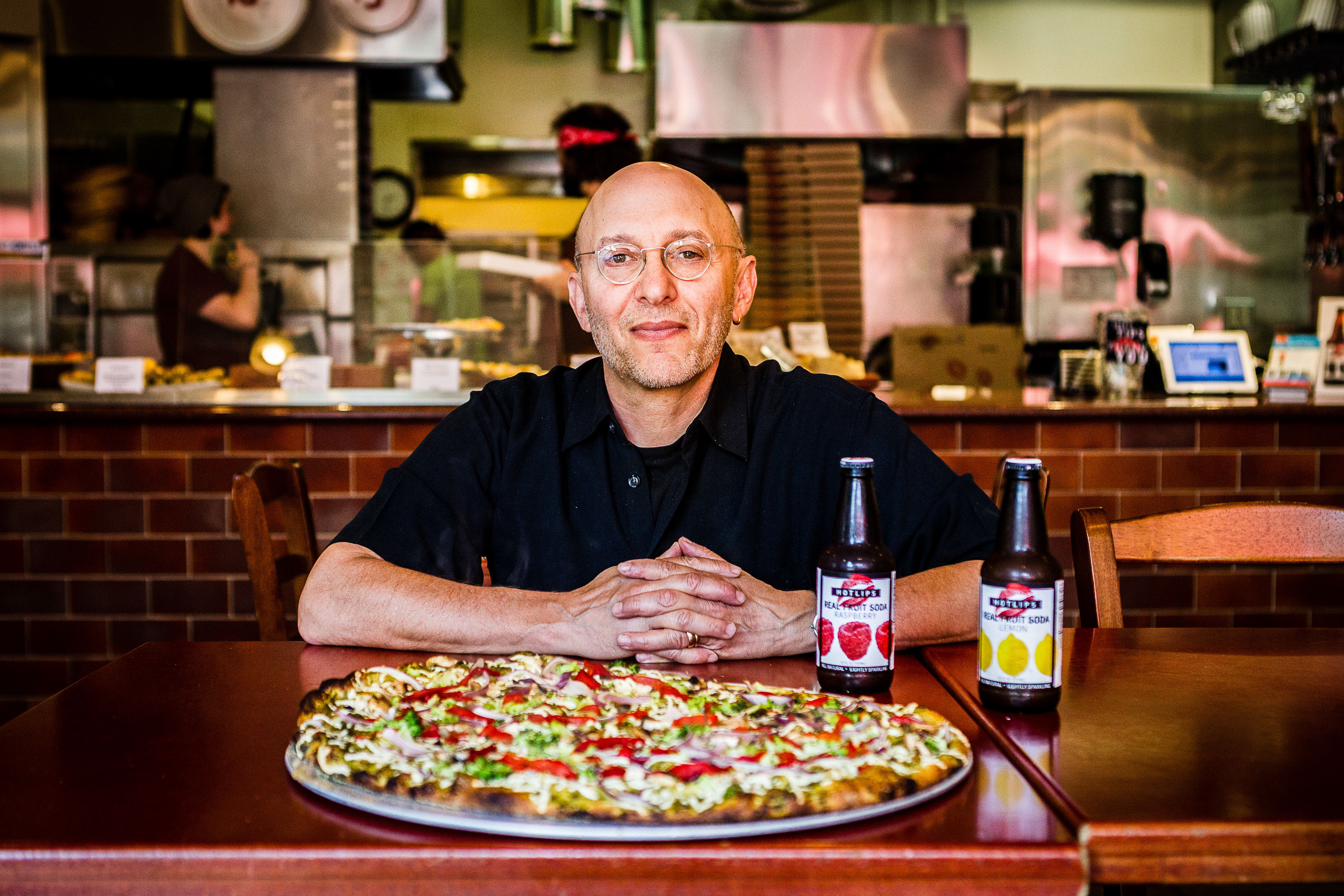 David Yudkin, Founder of Hot Lips Pizza pictured behind pizza pie