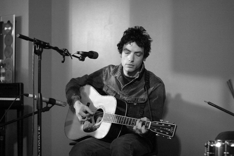 Jakob Dylan strumming guitar during a live performance for Kink 101.9 fm