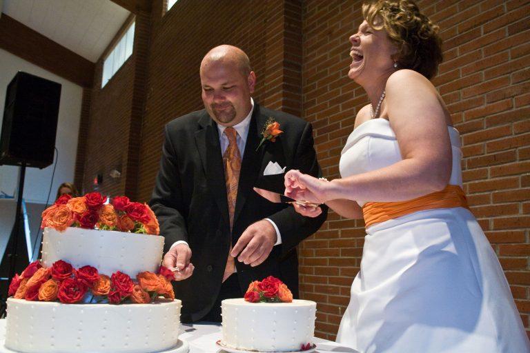 Brid and  groom laugh during portland wedding cake cutting